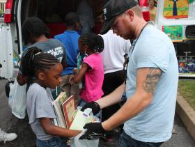 Sweet Reads' Kevin Korinek helps kids at Spanish Cove Apartments search for books.