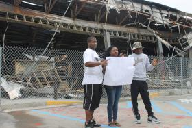 A group of visitors pose in front of the QuikTrip that burned down after Michael Brown died.