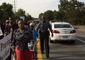 Mo. State Highway Patrol Capt. Ron Johnson joins a march of youth and pastors to a looted QuikTrip in Ferguson on August 14, 2014.