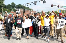 Protestors march toward the Ferguson Police station on Monday.