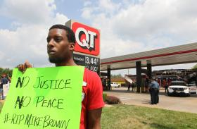 Protestor Allen Smith holds his sign up for passing traffic as he stands outside of the QuikTrip Gas station that was burned down in Ferguson. It may be awhile before investigators determine whether to bring state or federal charges against a Ferguson police officer who shot and killed 18-year-old Michael Brown.