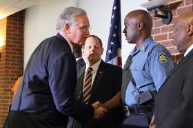 Missouri Governor Jay Nixon shakes the hand of Missouri Highway Patrol captain Ron Johnson after announcing that Jackson will head up law enforcement activities for the patrol in Ferguson.