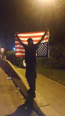 Timothy Booker said he would leave if police told him to, but hangs flag upside down because he says that's how the justice system is.