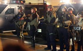 Police stand in line with weapons drawn as protesters gather on the streets of Ferguson, Missouri on August 18, 2014.