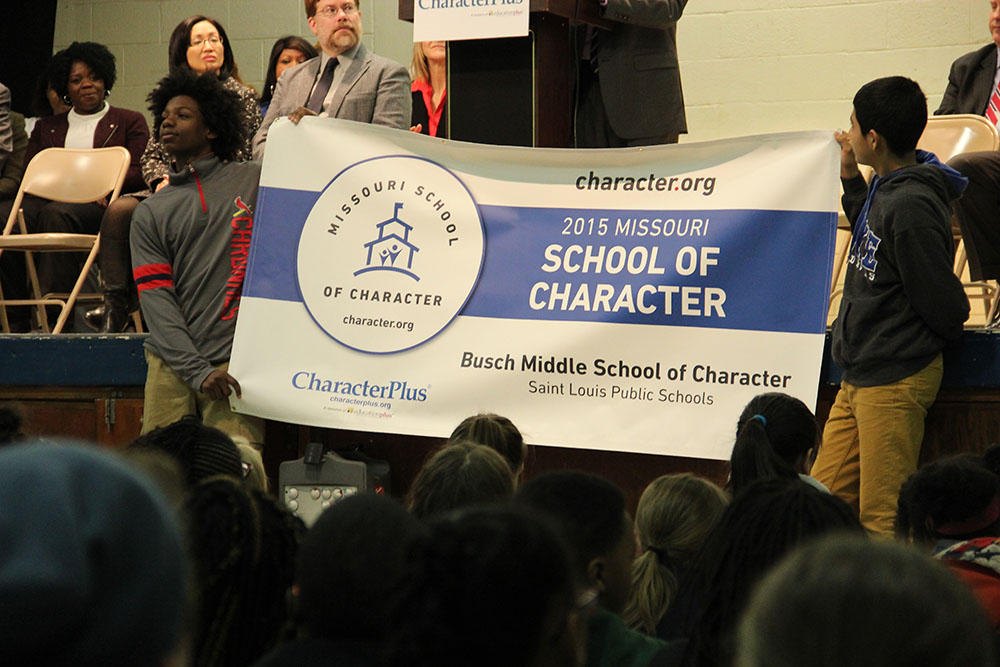 "Students at Busch Middle School of Character hold up a banner to celebrate the school being named a ""Missouri School of Character"""
