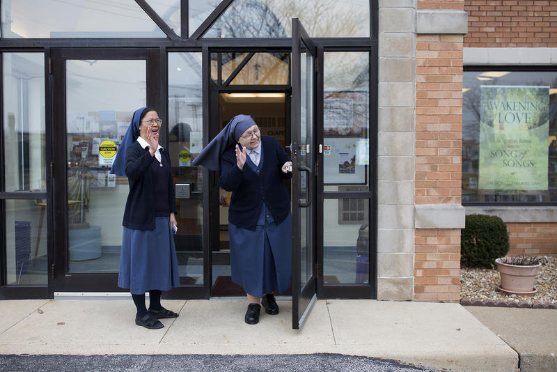 Sister An Mei, left, and Sister Mary Lea Hill wave to a group of high school students who recently visited the Pauline Books and Media store in Crestwood.