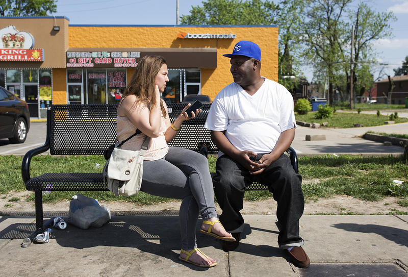 Lindy Drew sits at a bus stop on North Grand Boulevard. with St. Louis resident Bryan Gordon after approaching him about her social media photo project, Humans of St. Louis.