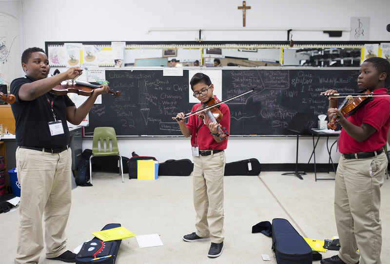 Students get ready for a violin class taught by Philip Tinge at Sister Thea Bowman Catholic School in East St. Louis.
