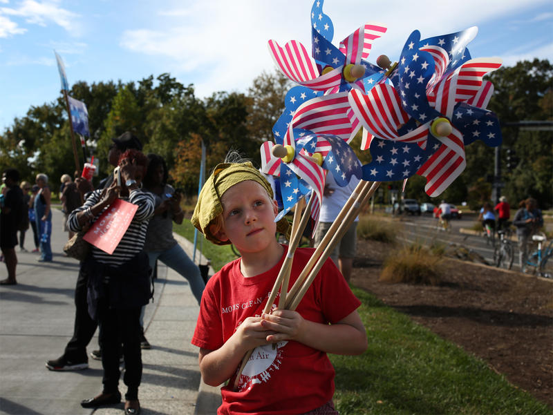 "Reny Alfonso, 7, carries American flag pinwheels at the ""Forward Together"" bus tour kickoff event outside the Missouri History Museum Sunday afternoon."
