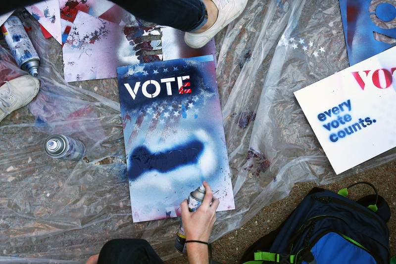 Students make signs on campus at Washington University before the start of the presidential debate on Sunday.