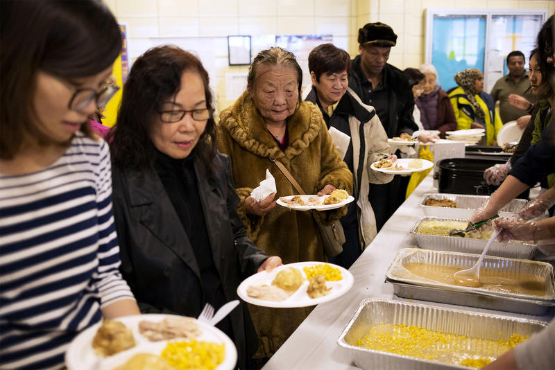 Dozens of people line up for a Thanksgiving dinner-style meal organized for immigrants and refugees at the International Institute of St. Louis on Nov. 20, 2018.