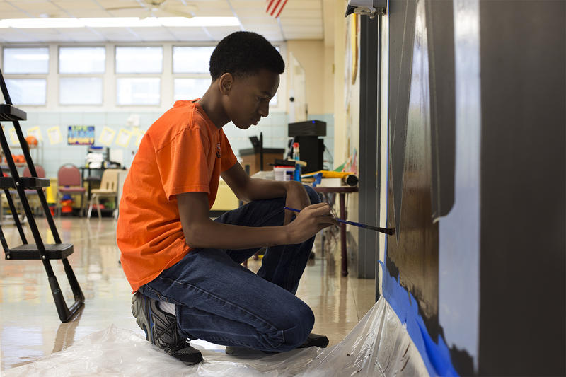 Darion Taylor, 15, helps paint a cafeteria mural at Confluence Academy's South City campus. Volunteers gathered to paint base coats for artist Cbabi Bayoc's design, which promotes healthy food.