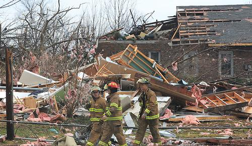 Sunset Hills firefighters survey the damage from the New Year's Eve tornado. A woman injured in the storm has died.
