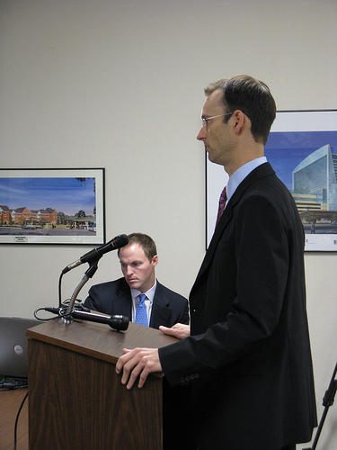 Cardinals president Bill DeWitt addresses the city's Downtown Economic Stimulus Authority on the progress of Ballpark Village. Chase Martin, with developer Cordish Companies, is seated.