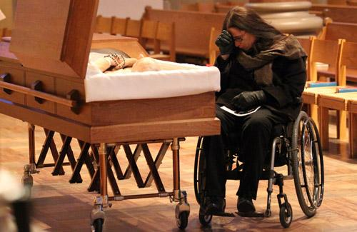 Marca Bristo, president of Access Living in Chicago, pauses in thought in front of the casket of Max Starkloff, an activist for disability rights, during his funeral in St. Louis on January 4, 2011. (Bill Greenblatt / UPI)