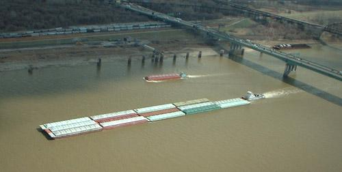 Barges pass under the Poplar Street Bridge. (via Wikimedia Commons/ Bachrach44)