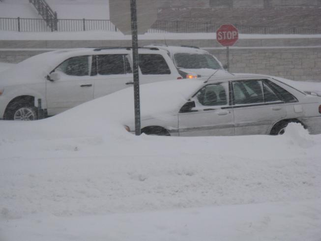 Snow partially buries a car in the media parking lot at the Mo. Capitol.