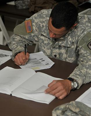 A soldier studies his notes during training in Djibouti. Far away from Djibouti, a group of military veterans is suing the trustees of several Missouri colleges, alleging the institutions systematically overcharged them.