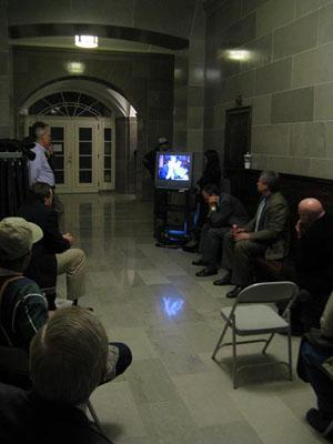 A TV was set up in a hallway of the State Capitol for those who couldn't get into the hearing room for a hearing on charging customers for a site permit for a proposed nuclear power plant.