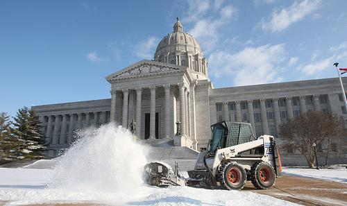 A worker clears snow at the Missouri State Capitol building after three inches of snow blanketed the city.