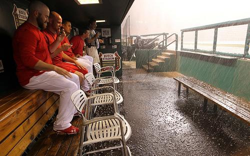 Members of the St. Louis Cardinals take refuge from the rain and hail that pounded the St. Louis area Tuesday night, causing damage and power outages and delaying the start of the game against the Washington Nationals.