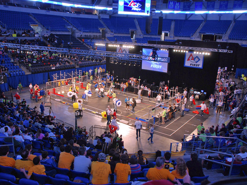 Spectators watch as participants prepare the field for a FIRST Robotics Regional competition match at Saint Louis University's Chaifetz Arena.