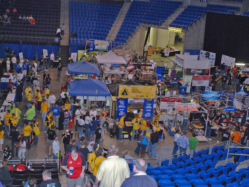 In the pit area, the FIRST Robotics teams prepare their robots for competition.