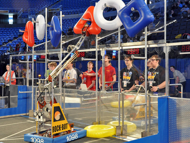 The goal of this year's FIRST Robotics competition is for robots to hang inner-tube-like shapes on pegs to form the FIRST logo (red triangle, white circle, and blue square).