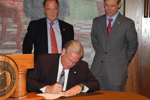 "Mo. Gov. Jay Nixon signs the ""Missouri Solution,"" flanked l-r by State Rep. Paul Quinn (D, Monroe City) and Mo. Dept. of Agriculture Director Dr. Jon Hagler."
