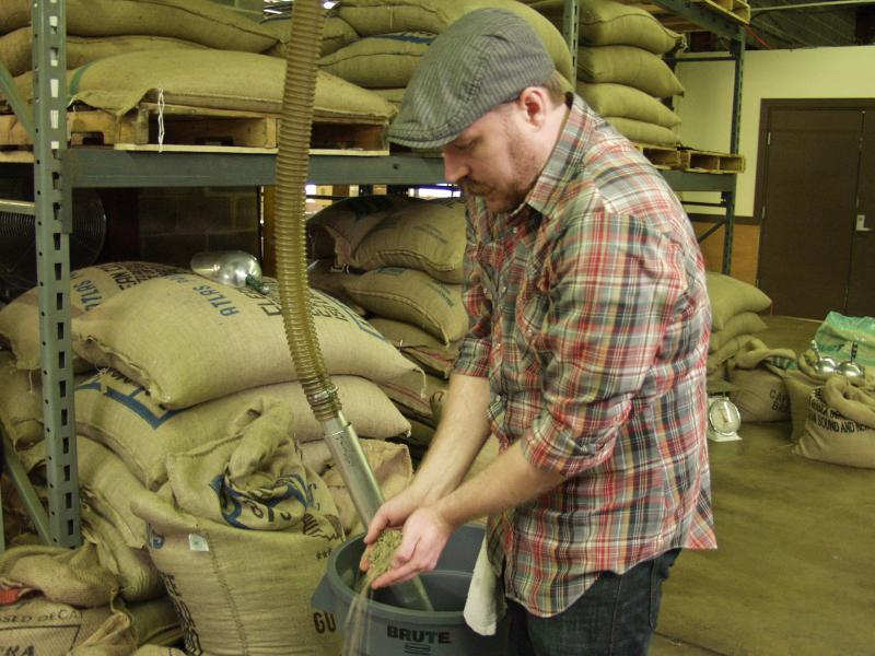 Morrocco examines un-roasted beans at Kaldi's Coffee headquarters. (Libby Franklin)