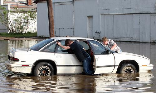 Young boys attempt to push a car from flood waters in downtown Poplar Bluff, Missouri on April 26, 2011. A levee on the Black River protecting the area from major flooding has breached in several places, forcing authorities to evacuate residents.