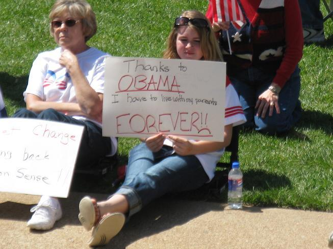 Abigail Paul, 11, of Kansas City sits with her grandmother and holds a sign during the Tea Party-backed rally.