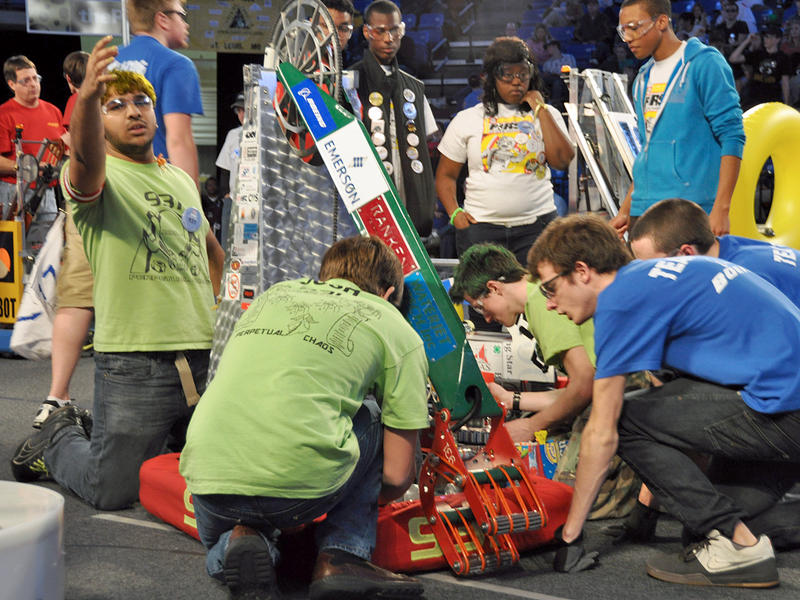 Team members from the Ratchet Rockers (Wentzville School District, in blue) Rob Fletcher (front) and Matt Moore help Perpetual Chaos team members (in green) repair their robot.