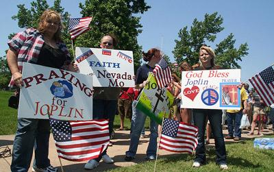 People from around the state of Missouri held signs of support before the start of a memorial service for the dead and missing in Joplin, Mo. on May 29.