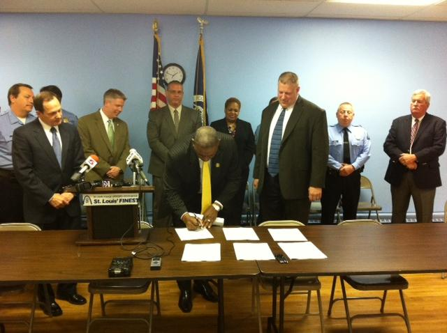 Members of the St. Louis Police Board of Commissioners and Mayor Francis Slay sign the police union contract.