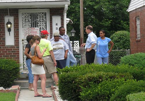 Mayor Francis Slay (right) and human services director Bill Siedhoff (red cap) speak with residents on Dryden Ct. who were affected by flash flooding. The sign says the house has been condemned.