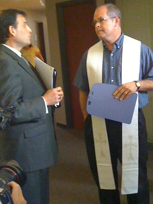 Rev. Kevin Cameron, senior pastor at Parkway United Church of Christ, delivers a letter to Steve Taylor, press secretary for Congressman Todd Akin.
