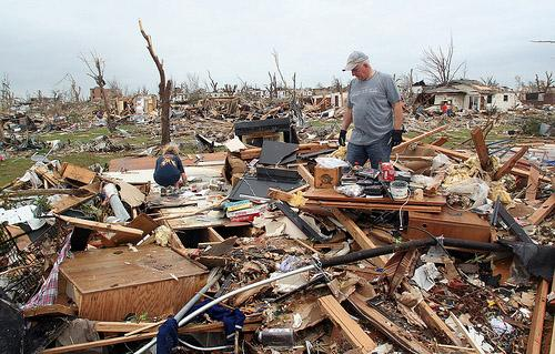 A man sorts through what is left of a home in Joplin, Mo. on May 24, 2011. The tornado that swept through the area has left a confirmed 134 people dead, officials announced today.
