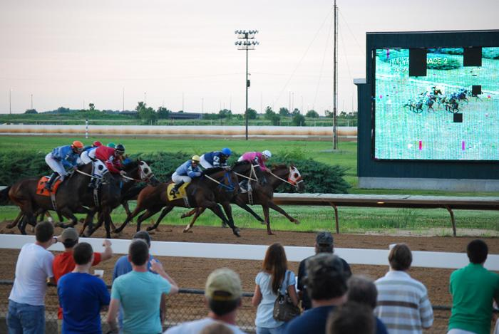Horses race to the finish line at Fairmount Park Racetrack on a recent Friday night. The Jumbotron shows the action, and its age in the background.