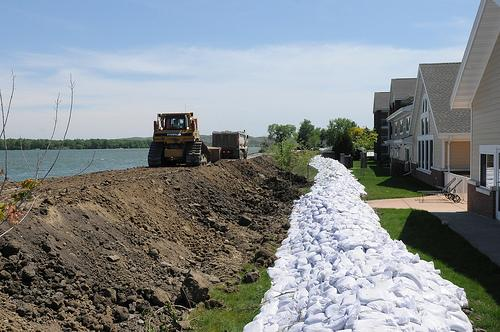 PIERRE, S.D. – A contractor packs down mud to strengthen the levee and a berm of sandbags line local residential and businesses to help contain the rising Missouri River in Pierre, June 1, 2011.