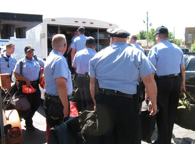 St. Louis police officers load their gear into a van as they prepare to leave for Joplin.