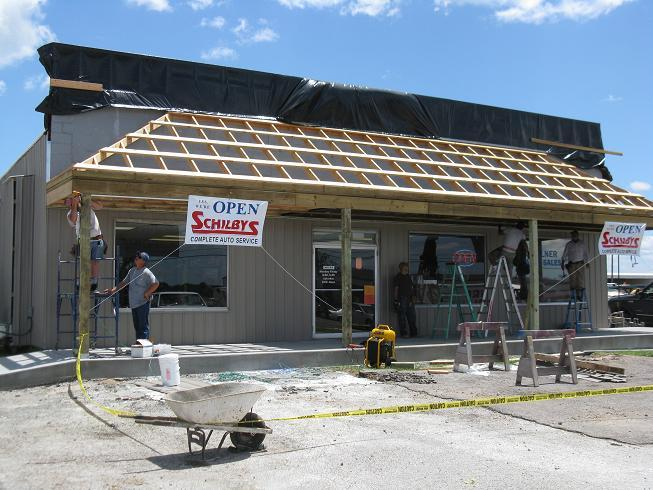 Workers make repairs to an auto service shop in Sedalia that was damaged by a tornado on May 25th.