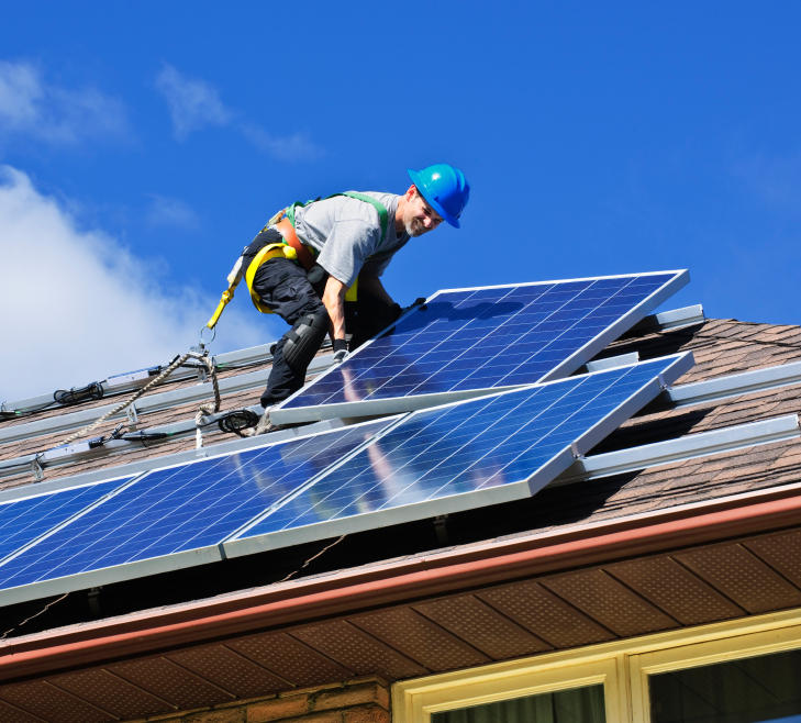 A worker installs rooftop solar panels.