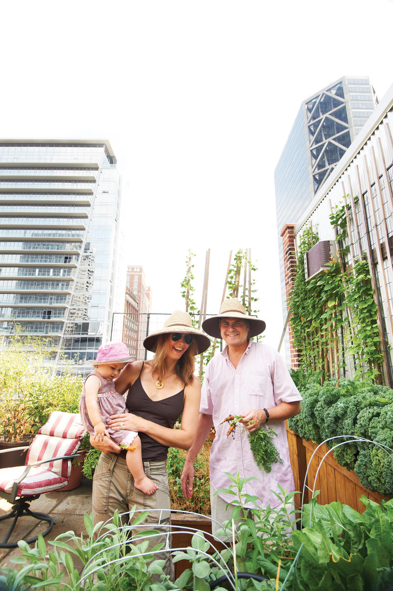 Natalie Semchyshyn, Amos Harris and their young daughter, Ember, atop the family's downtown rooftop garden.