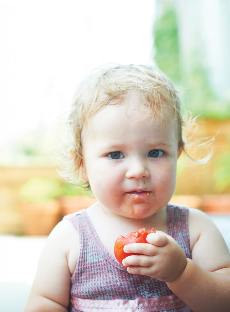 Ember, Amos Harris and Natalie Semchyshyn's daughter, enjoys a farm-fresh tomato from the sky-high edible paradise.