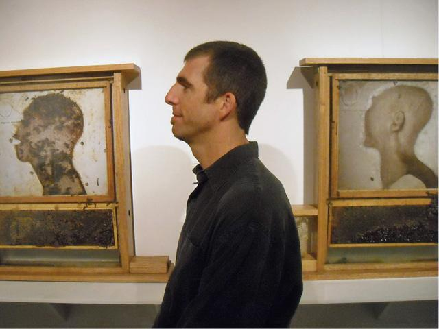 "Artist Brigham Dimick with part of ""Waxworks 2,"" a series of three self-portraits that include observation hives with live honeybees."