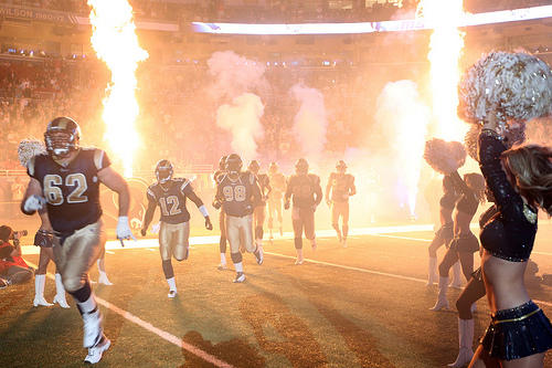 The St. Louis Rams enter the field for a game. A longtime equipment manager for the team has sued the Rams, alleging he was fired due to age discrimination.