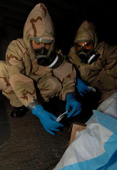 U.S. Navy personnel take samples from a mock anthrax pile during a Chemical, Biological, Radiological (CBR) decontamination drill aboard an aircraft carrier in the Persian Gulf in 2007.