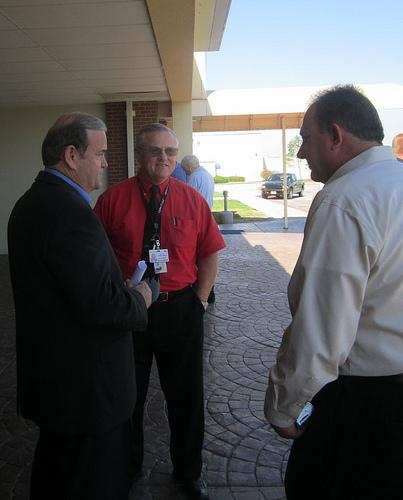 Jerry Costello (L) speaks with Downtown St. Louis Airport officials Robert McDaniel (center) and Mike Miller (R) after announcing he will not run for re-election on October 4, 2011.