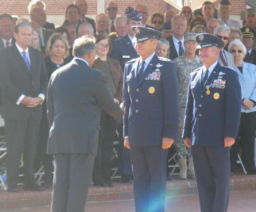 Defense Secretary Leon Panetta (L) shakes the hand of Gen. William Fraser (C) after Fraser assumed command of United States Transportation Command at Scott Air Force Base on Friday. Retiring Gen. Duncan McNabb is behind Fraser.